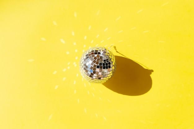Jedna kula dyskotekowa na rozświetlającym żółtym tle