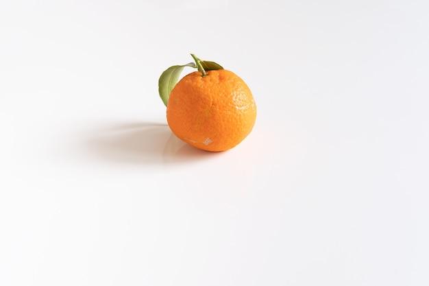 Jedna mandarynka lub mandarynka z zielonym liściem