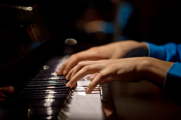 Jedna męska ręka na pianinie.