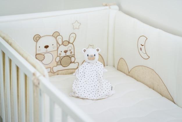 Jedna miękka zabawka białego misia w białym łóżku dziecięcym