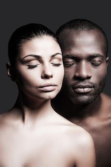 Jedna miłość. afrykański mężczyzna bez koszuli i kaukaska kobieta łączą twarze i mają zamknięte oczy, stojąc na szarym tle