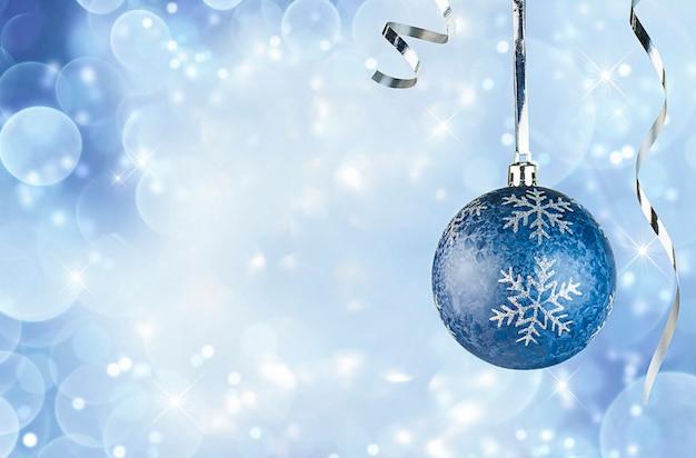 Jedna niebieska ozdoba świąteczna na niebieskim nieostrym tle