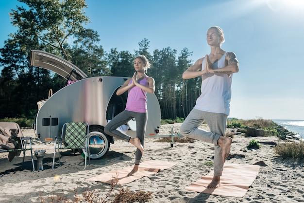 Jedną nogą. kochająca zdrowa para stojąca na jednej nodze podczas porannej jogi w pobliżu ich mobilnego domu