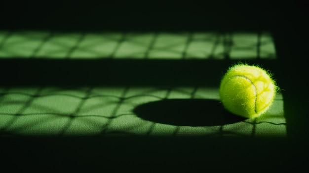Jedna nowa piłka tenisowa i cień netto na zielonym, twardym korcie ze światłem z prawej strony