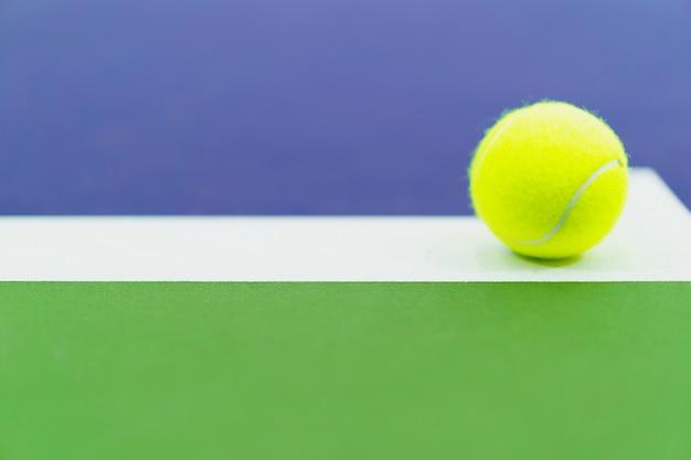 Jedna nowa piłka tenisowa na białej linii w niebieskim i zielonym twardym korcie, miejsce po lewej stronie