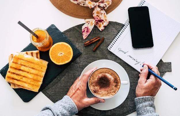 Jedna osoba gotowa na śniadanie. biały kubek z cappuccino, kawą i domowym mlekiem. plastry tostów z dżemem.