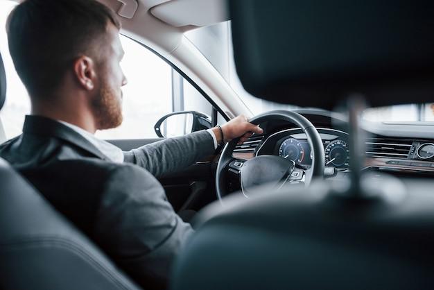 Jedna osoba. nowoczesny biznesmen próbuje swojego nowego samochodu w salonie samochodowym