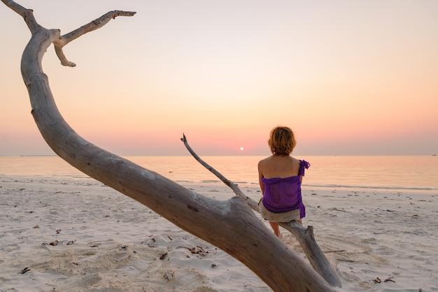 Jedna osoba siedzi na gałęzi piaszczystej plaży romantyczne niebo o zachodzie słońca, sylwetka widok z tyłu, złote światło słoneczne, prawdziwi ludzie. indonezja, wyspy kei, moluccas maluku
