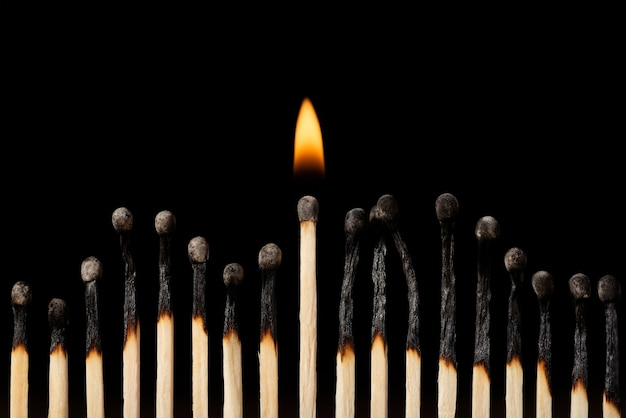 Jedna płonąca zapałka w jednej linii z innymi spalonymi czarnymi zapałkami