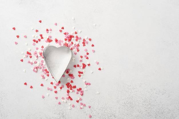 Jedna pusta foremka do ciastek w kształcie serca z rozrzuconymi wielobarwnymi słodyczami do pieczenia na różowym tle.