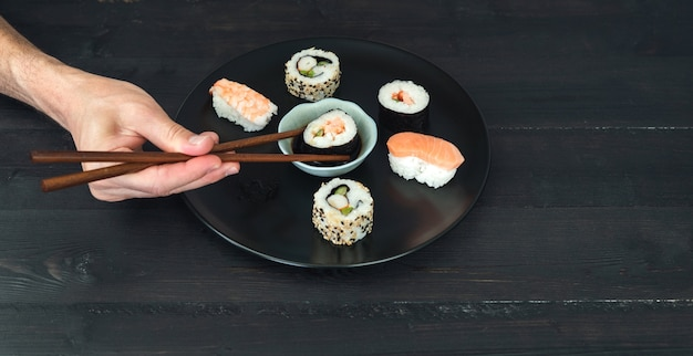 Jedną ręką maczanie bułki sushi w sosie