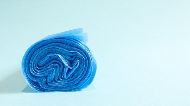Jedna rolka plastikowych worków na śmieci w kolorze niebieskim na niebieskim tle. worki, które są zaprojektowane tak, aby pomieścić w nich śmieci i używane w domu i umieszczane w różnych pojemnikach na śmieci. skopiuj miejsce.