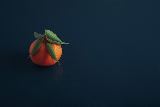 Jedna świeża dojrzała mandarynka na białym tle na starym drewnianym stole rustykalnym, pomalowana na niebiesko