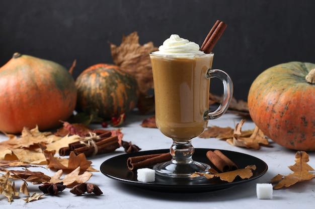 Jedna szklana filiżanka latte z dyni z przyprawami i kremową pianką na ciemnym tle z dyniami i jesiennymi liśćmi. format poziomy