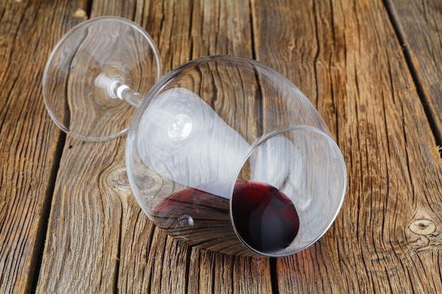 Jedna szklanka połowa czerwonego wina na drewnianym stole