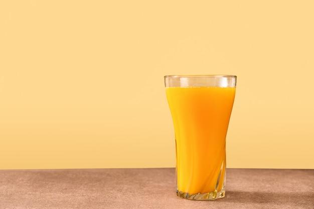 Jedna szklanka soku pomarańczowego na jasnożółtym tle