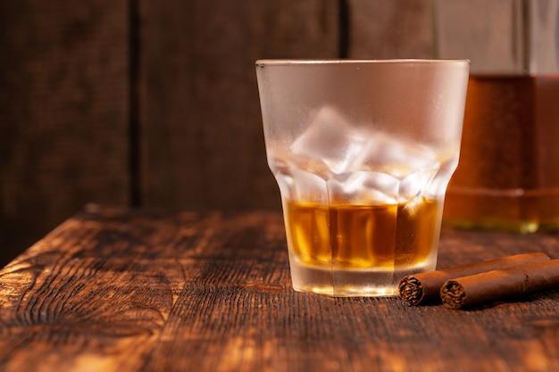 Jedna szklanka whisky i cygaro na drewnianym stole