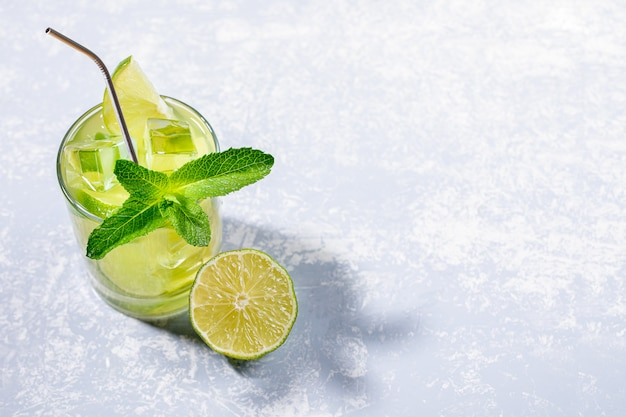 Jedna szklanka z mrożoną zieloną herbatą matcha z limonką, lodem, miętą i metalową słomką do picia na szaro z miejsca na kopię.