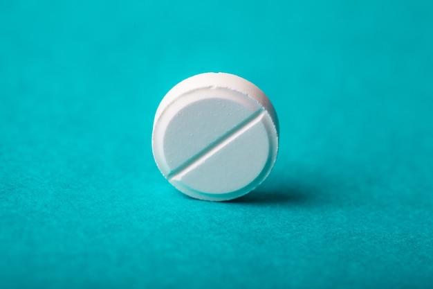 Jedna tabletka zbliżenie na tle z paczką pigułek