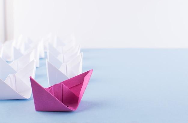 Jedna wyjątkowa różowa łódź papierowa wśród wielu. różne statki papierowe jako koncepcja indywidualności i przywództwa