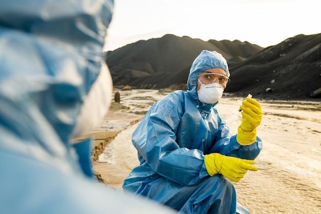 Jedna z dwóch młodych ekologów w gumowych rękawiczkach, kombinezonach ochronnych, okularach i respiratorach trzymająca próbkę toksycznej wody
