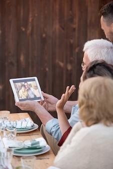 Jedna z kobiet macha ręką do młodej pary na ekranie tabletu