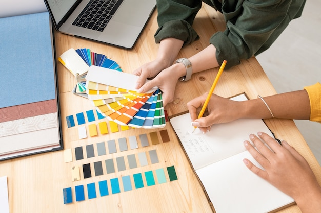 Jedna z młodych projektantek trzyma paletę kolorów nad stołem, podczas gdy jej koleżanka robi notatki podczas pracy nad nowym zamówieniem