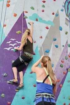 Jedna z młodych sportsmenek trzyma linę asekuracyjną, a druga porusza się w górę po ściance wspinaczkowej podczas treningu