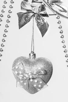 Jedna zabawka świąteczna srebrne świecące serce z kokardą wiszącą na srebrnych gałązkach z drewna z bliska. orientacja pionowa.
