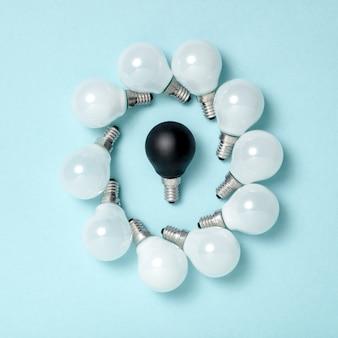Jedna żarówka wyróżniająca się, świecąca inaczej. koncepcje pomysłów na kreatywność w biznesie. płaski układ