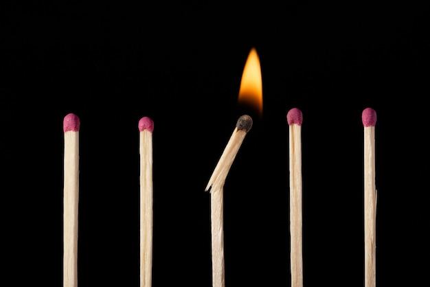 Jedna zepsuta płonąca zapałka na równi z innymi zwykłymi niezapalonymi zapałkami