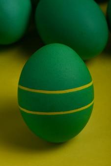 Jedna zielona pisanka z dwoma żółtymi paskami stoi przed zielonymi jajkami na żółtym tle