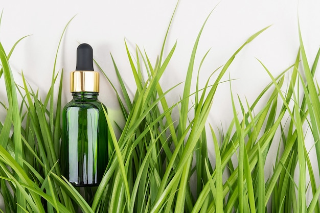 Jedna zielona szklana butelka z serum, olejkiem eterycznym, kolagenem lub innym produktem kosmetycznym wśród zielonej trawy na białym tle. natural organic spa kosmetyczna koncepcja makieta widok z góry.
