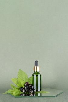 Jedna zielona szklana butelka z serum, olejkiem eterycznym lub innym produktem kosmetycznym z gałązką czarnej porzeczki
