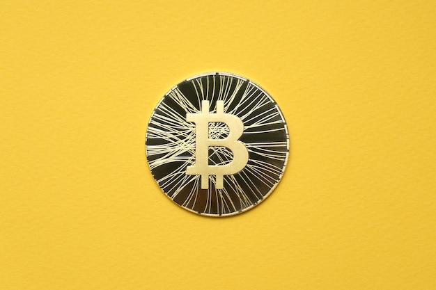 Jedna złota moneta bitcoin leży na żółtym tle