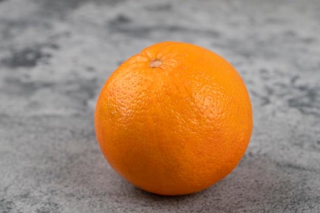 Jedno całe świeże zdrowe pomarańcze na białym tle na kamiennym stole.