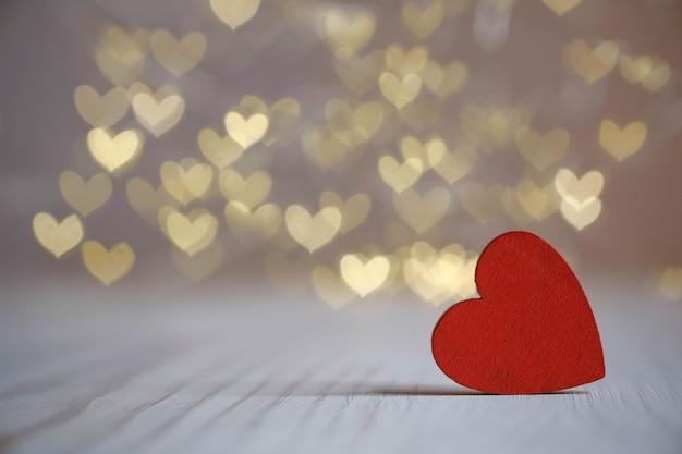 Jedno czerwone drewniane serca na tle bokeh