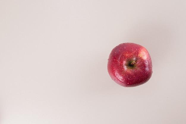 Jedno czerwone jabłko na białej powierzchni.