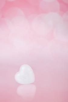 Jedno małe białe serce na różowym tle bohe