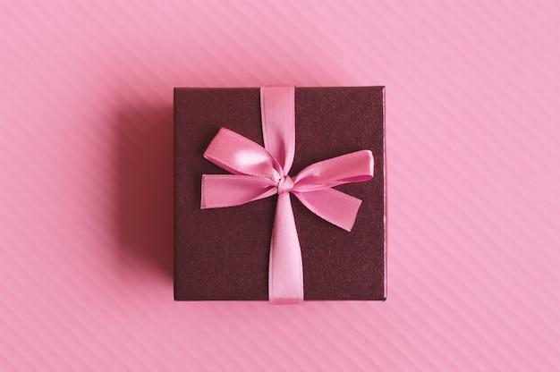 Jedno małe ozdobne pudełko z różową wstążką na różowym tle