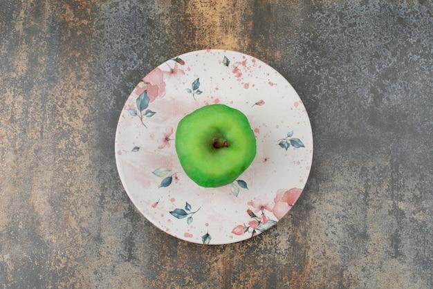 Jedno obrane zielone jabłko na pięknym talerzu na marmurowej powierzchni.