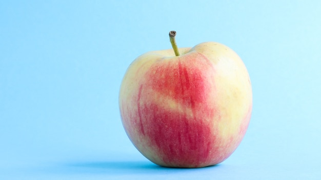 Jedno piękne, apetyczne i świeże jabłko na niebieskim tle. koncepcja zdrowej słodkiej żywności.