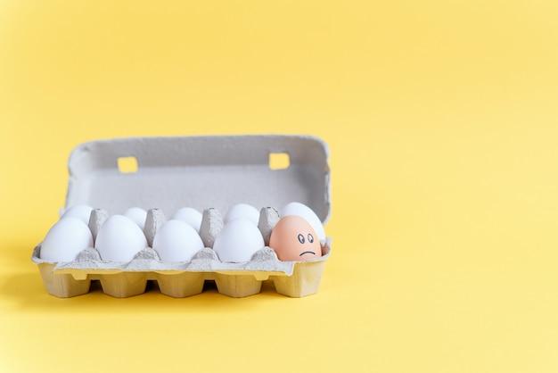 Jedno pomarańczowe jajko z rysowaną smutną twarzą wśród białych jajek na tekturowej tacy. różni się od innych.