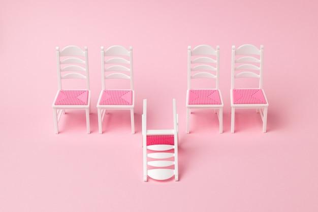 Jedno przewrócone krzesło i cztery krzesła stojące w rzędzie