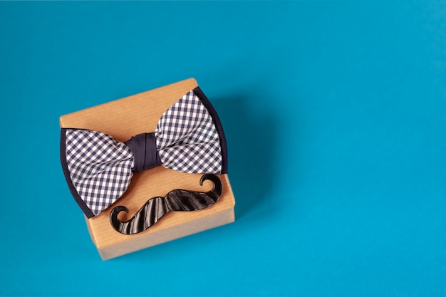 Jedno pudełko upominkowe owinięte papierem rzemieślniczym i przewiązane muszką na niebiesko.