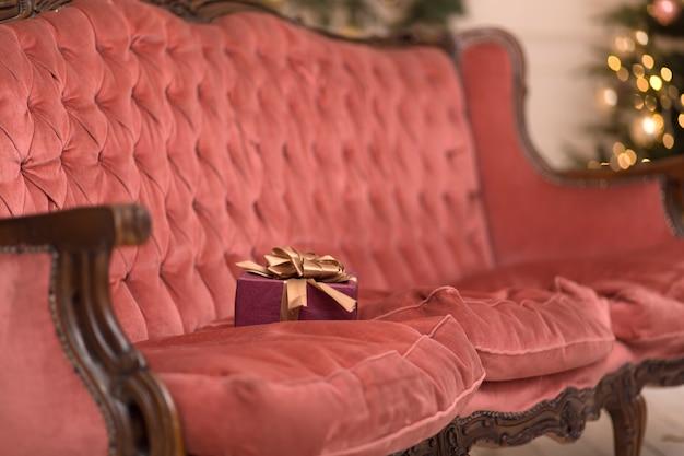 Jedno pudełko z prezentem na boże narodzenie leży na sofie w stylu retro