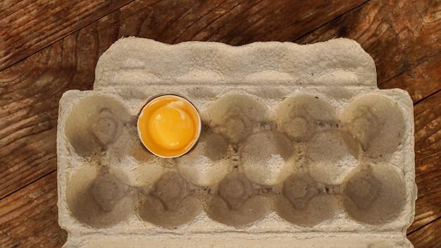 Jedno rozbite jajko w tekturowej tacy na jajka. pół jajka z żółtkiem w pustym pudełku na drewnianym tle