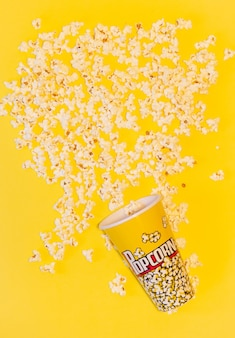 Jedno wiadro popcornu przewrócone, otoczone wieloma popcornami na żółtym tle