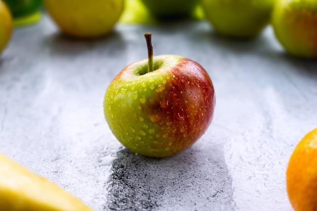 Jedno zielone dojrzałe jabłko leży na szarej powierzchni, na pierwszym planie mała rozmazana część banana i mandarynki, w tle część rozmytych zielonych jabłek