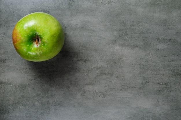Jedno zielone jabłko na ciemnym kamieniu, widok z góry.